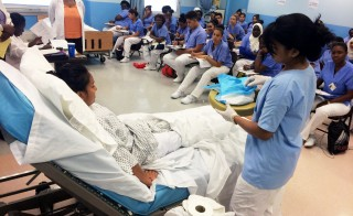High school students hoping to earn their certified nursing assistant license practice skills they will need to pass the state exam during a 10-week course at Hostos Community College in the Bronx. Photo by Meredith Kolodner/Hechinger Report.