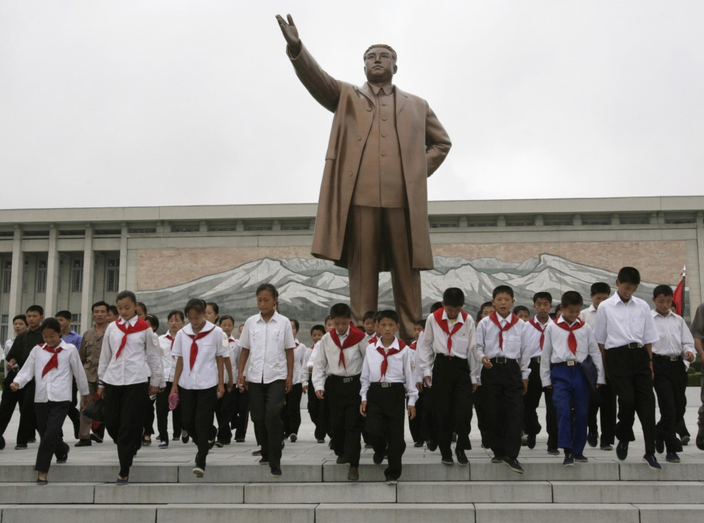 North Korean children wearing the uniform of a communist youth organisation walk away after paying their respects at the statue of Kim Il-Sung in Pyongyang August 27, 2007. Picture taken August 27, 2007.    REUTERS/Reinhard Krause (NORTH KOREA) - RTR1T73H