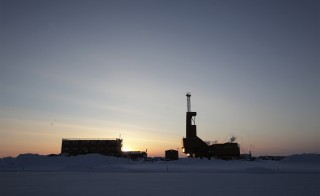 The sun sets behind an oil drilling rig in Prudhoe Bay, Alaska on March 17, 2011. Photo by Lucas Jackson/Reuters