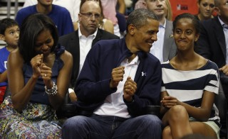 U.S. President Barack Obama and first lady Michelle Obama (L) move to the music as daughter Malia (R) looks on as they attend the Olympic men's exhibition basketball game between Team USA and Brazil in Washington July 16, 2012.  REUTERS/Kevin Lamarque (UNITED STATES - Tags: POLITICS SPORT BASKETBALL OLYMPICS TPX IMAGES OF THE DAY) - RTR34ZXX
