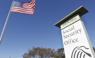 An American flag flutters in the wind next to the sign for a Social Security Administration office in Burbank, California October 25, 2012. Photo by Fred Prouser/Reuters