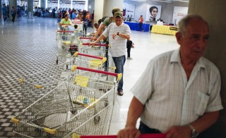 "Customers line up to get in for shopping at a state-run Bicentenario supermarket in Caracas May 2, 2014.  President Nicolas Maduro is introducing a controversial shopping card intended to combat Venezuela's food shortages but decried by critics as a Cuban-style policy illustrating the failure of his socialist policies. Maduro, the 51-year-old successor to Hugo Chavez, trumpets the new ""Secure Food Supply"" card, which will set limits on purchases, as a way to stop unscrupulous shoppers stocking up on subsidized groceries and reselling them. REUTERS/Jorge Silva (VENEZUELA - Tags: POLITICS BUSINESS SOCIETY TPX IMAGES OF THE DAY) - RTR3NL83"