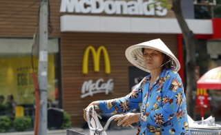 A woman wearing a traditional Vietnamese hat pushes her bicycle past a McDonald's restaurant in Saigon on March 9, 2015. Photo by Kham/Reuters