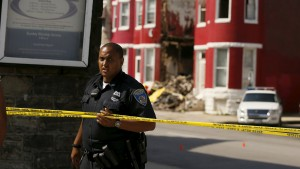 A Baltimore police officer guards a crime scene where orange cones mark the site of shell casings that were found at the scene of a shooting at the intersection of West North Avenue and Druid Hill Avenue in West Baltimore, Maryland May 30, 2015. Local media have reported more than 35 murders in the city of Baltimore since the April rioting over the death of 25-year-old resident Freddie Gray and shootings continue regularly in his West Baltimore neighborhood.  REUTERS/Jim Bourg - RTR4Y6CN