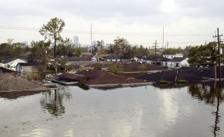 Only the rooftops of houses are seen with the skyline in the background in flooded New Orleans August 30, 2005. Floodwaters engulfed much of New Orleans on Tuesday as officials feared a steep death toll and planned to evacuate thousands remaining in shelters after the historic city's defenses were breached by Hurricane Katrina. REUTERS/Rick Wilking  RTW/PN - RTRLZED
