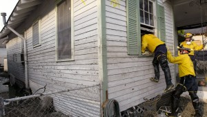 Robert Young is helped through a window by members of the FEMA Urban Search and Rescue Missouri task force while searching through homes during their door to door search for survivors or human remains near Lake Pontchartrain in New Orleans, September 17, 2005. REUTERS/J.P. Moczulski  JPM/PN - RTROF4R