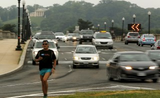 A jogger keeps ahead of morning rush hour traffic on the Memorial Bridge in Washington, D.C. Traffic deaths were up 14 percent nationally in the first six months of this year, according to data gathered by the National Safety Council. Photo by Gary Cameron/Reuters