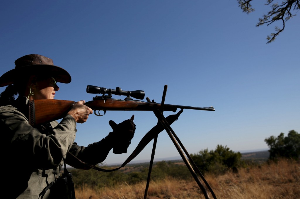 Professional hunter CEO of PHASA (Professional hunters association of South Africa), Adri Kitshoff, takes aim during a hunt for game at the Iwamanzi Game Reserve in Koster, in the North West Province, June 6, 2015. Africa's big game hunting industry helps protect endangered species, according to its advocates. Opponents say it threatens wildlife. Now a mooted change in regulations in the United States could affect the number of foreigners who come to Africa to hunt big game, damaging the industry and possibly hurting wildlife. Picture taken June 6, 2015. REUTERS/Siphiwe Sibeko  - RTX1G43M