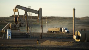 A service truck drives past an oil well on the Fort Berthold Indian Reservation in North Dakota, November 1, 2014. The Fort Berthold Indian Reservation, home to the Mandan, Hidatsa, and Arikara Nation, produces nearly a third of North Dakota's oil. The election for a new tribal chairman, in which both candidates have positioned themselves as reformers, may change the oil industry's relationship with the reservation. Photo taken November 1, 2014.  REUTERS/Andrew Cullen   (UNITED STATES - Tags: POLITICS ELECTIONS ENERGY BUSINESS) - RTX1KAIK