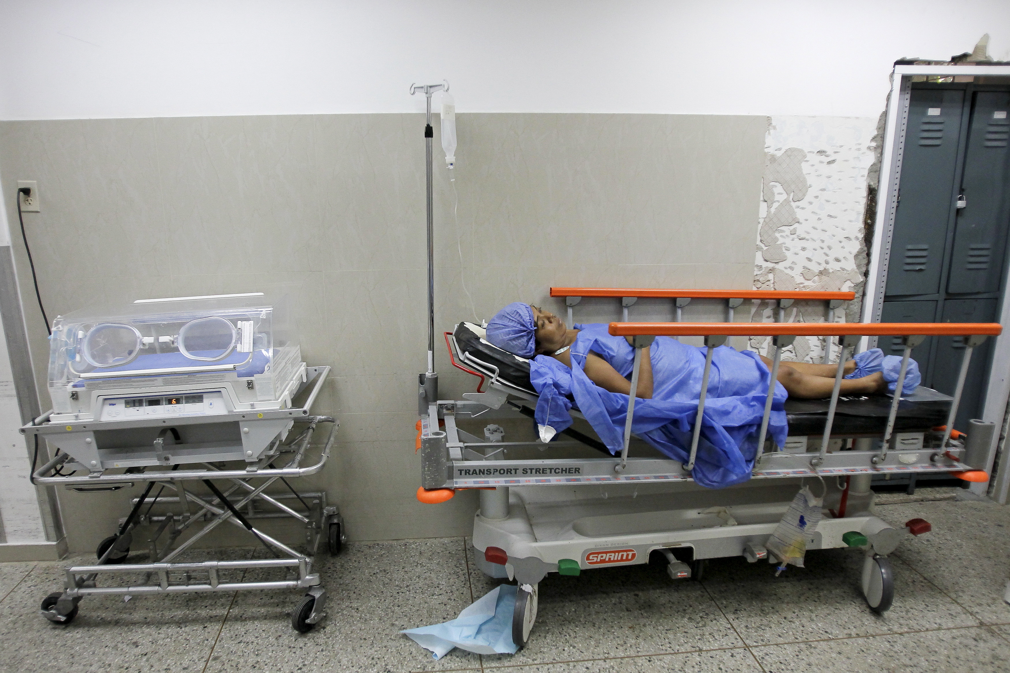 A woman lays on a hospital bed without sheets as she recovers after labor at a maternity hospital in Maracaibo, Venezuela, June 19, 2015. Chronic shortages of important health and food necessities have plagued Venezuela since the start of an economic crisis in the country, partly caused by low oil prices. Photo by Isaac Urrutia/Reuters