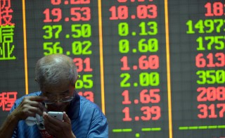 An investor checks on his mobile phone in front of an electronic board showing stock information at a brokerage house in Hangzhou, Zhejiang province, China, July 29, 2015.  Beijing may be struggling to put a floor under its tumbling stock market but it has managed to lock the yuan into an incredibly tight band against the dollar, despite pledging again to allow more exchange rate volatility. REUTERS/Stringer CHINA OUT. NO COMMERCIAL OR EDITORIAL SALES IN CHINA   - RTX1M7GA