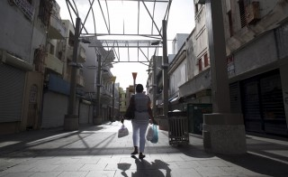 A woman carries bags while walking in a commercial area with stores either closed or offered for sale in San Juan, Puerto Rico, July 31, 2015. Puerto Rico will miss a payment on debt due August 1, the governor's chief of staff said on Friday, an event that will be considered a default by investors as the commonwealth lurches towards what could be one of the largest U.S. municipal debt restructurings in history. The island faces a number of debt payments that day but had signaled in recent weeks that it may miss the $58 million payment on Public Finance Corporation (PFC) bonds. REUTERS/Alvin Baez  - RTX1MMK6