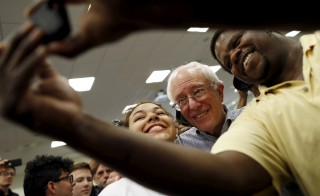 Vermont Senator and U.S. Democratic presidential candidate Bernie Sanders snaps a selfie with supporters at a campaign town hall in Manchester, New Hampshire, August 1, 2015.  REUTERS/Dominick Reuter - RTX1MP2M
