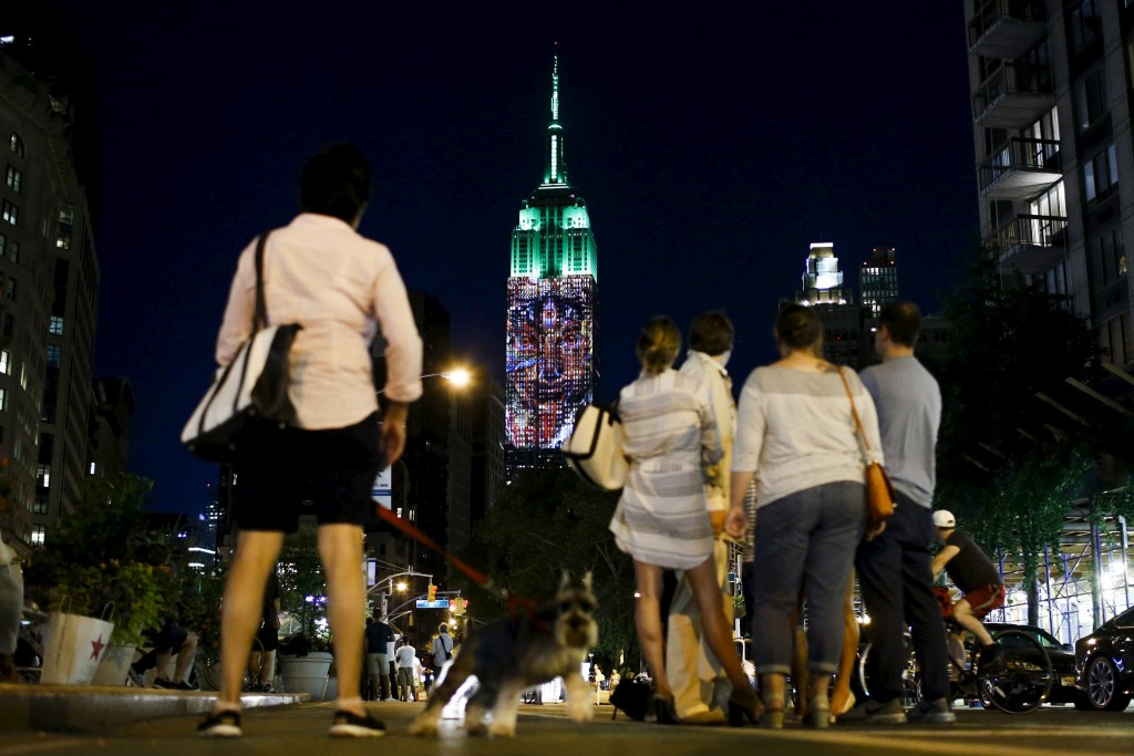 People watch as an image is projected onto the Empire State Building in New York August 1, 2015. Photo by Eduardo Munoz/Reuters.
