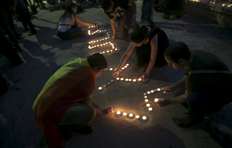"""People use candles to spell out the phrase """"Thou shalt not kill"""" in Hebrew at a candlelight vigil for Shira Banki in Tel Aviv, Israel, August 2, 2015. Banki died Sunday of stab wounds sustained when an ultra-Orthodox man with a knife attacked a Gay Pride parade in Jerusalem Thursday. Photo by Baz Ratner/Reuters"""