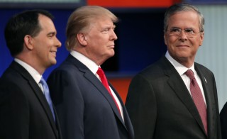 Republican 2016 presidential candidate and former Florida Governor Jeb Bush (R) looks over at businessman Donald Trump (C) and Wisconsin Governor Scott Walker (L) as the candidates pose with seven other candidates at the first official Republican presidential candidates debate of the 2016 U.S. presidential campaign in Cleveland, Ohio, August 6, 2015. REUTERS/Brian Snyder  - RTX1NE3O