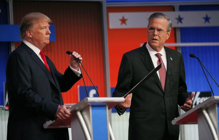 Republican 2016 presidential candidates, businessman Donald Trump (L) and former Florida Governor Jeb Bush, take their places at their podiums before the start of the first official Republican presidential candidates debate of the 2016 U.S. presidential campaign in Cleveland, Ohio, August 6, 2015. Photo by Brian Snyder/Reuters.