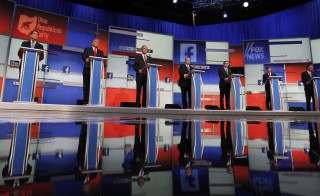 Republican 2016 presidential candidates (L-R) Wisconsin Governor Scott Walker, businessman Donald Trump, former Florida Governor Jeb Bush, former Arkansas Governor Mike Huckabee, U.S. Senator Ted Cruz, U.S. Senator Rand Paul and Ohio Governor John Kasich stand at their podiums at the first official Republican presidential candidates debate of the 2016 U.S. presidential campaign in Cleveland, Ohio, August 6, 2015. REUTERS/Aaron Josefczyk  - RTX1NE9Y