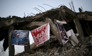 An Afghan civil society member hangs a banner on a destroyed building at the site of a truck bomb blast in Kabul, Afghanistan August 8, 2015. A wave of attacks in Kabul on Friday killed more than 40 people, including a U.S. soldier, and wounded hundred. Photo by Ahmad Masood/Reuters