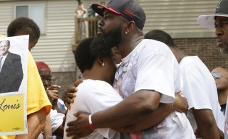 Michael Brown Sr. comforts his wife Cal Brown during a moment of silence to mark the first anniversary of the killing of his son Michael Brown, Ferguson, Missouri, August 9, 2015. Ferguson was the site of several events this weekend in commemoration of Brown's death. Photo by Rick Wilking/Reuters