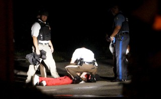A man lies on the ground after a police officer-involved shooting in Ferguson, Missouri on Aug. 9. The shooting took place after a day of peaceful events commemorating the fatal shooting of an unarmed black man by a white officer one year ago. Photo by Rick Wilking/Reuters