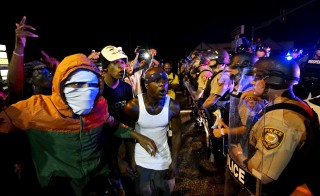 Protesters yell at a police line shortly before shots were fired in a police-officer involved shooting in Ferguson, Missouri August 9, 2015.  Two people were shot in the midst of a late-night confrontation between riot police and protesters, after a day of peaceful events commemorating the fatal shooting of Michael Brown by a white officer one year ago.  REUTERS/Rick Wilking      TPX IMAGES OF THE DAY      - RTX1NPUD