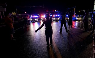 A protester yells at a police line shortly before shots were fired in a police-officer involved shooting in Ferguson, Missouri August 9, 2015.  Two people were shot in the midst of a late-night confrontation between riot police and protesters, after a day of peaceful events commemorating the fatal shooting of Michael Brown by a white officer one year ago.  REUTERS/Rick Wilking - RTX1NPUQ