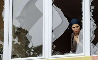 A woman looks out from a shattered window, damaged after an attack on a nearby police station in Istanbul, Turkey, on Aug. 10. Photo by Huseyin Aldemir/Reuters