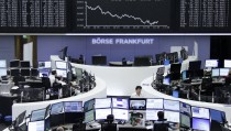 Traders are pictured at their desks in front of the DAX board at the stock exchange in Frankfurt, Germany August 11, 2015. European shares retreated on Tuesday, with carmakers and luxury goods stocks among the worst performers after China devalued its yuan currency. REUTERS/Remote/Pawel Kopczynski - RTX1NWXV