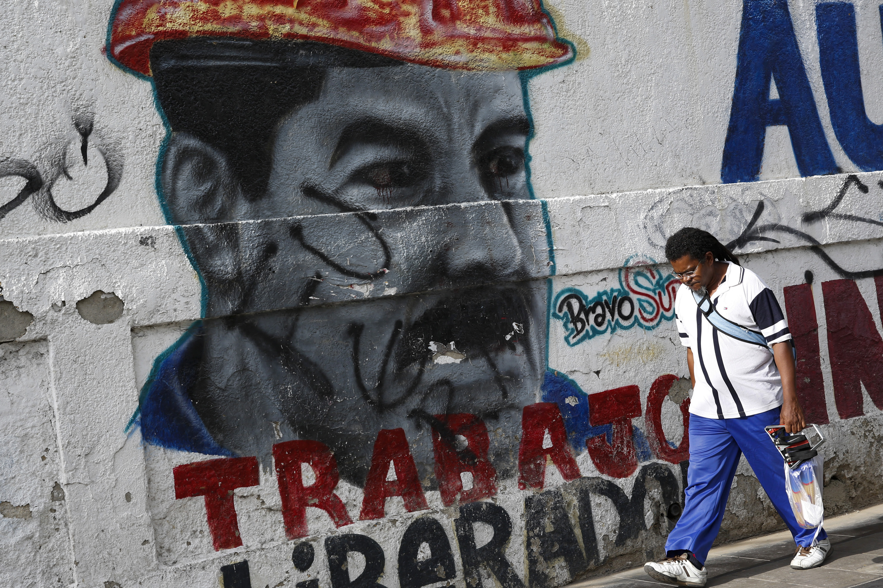 "A man walks past a mural depicting Venezuela's President Nicolas Maduro in Caracas, August 13, 2015. Maduro's popularity fell to 24.3 percent in July, hurt by voracious inflation and shortages of goods ranging from spare parts to shampoo, according to respected local pollster Datanalisis. The mural reads, ""Liberating work"". Photo by Carlos Garcia Rawlins/Reuters"