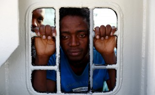 Migrants look out of a window on the Medecins Sans Frontiere (MSF) rescue ship Bourbon Argos as it arrives in Trapani, on the island of Sicily, Italy, August 9, 2015. The Mediterranean has become the world's most deadly border zone for migrants. More than 2,000 migrants and refugees have died so far this year in attempts to reach Europe by boat, the International Organization for Migration said last week. Photo by Darrin Zammit Lupi/Reuters