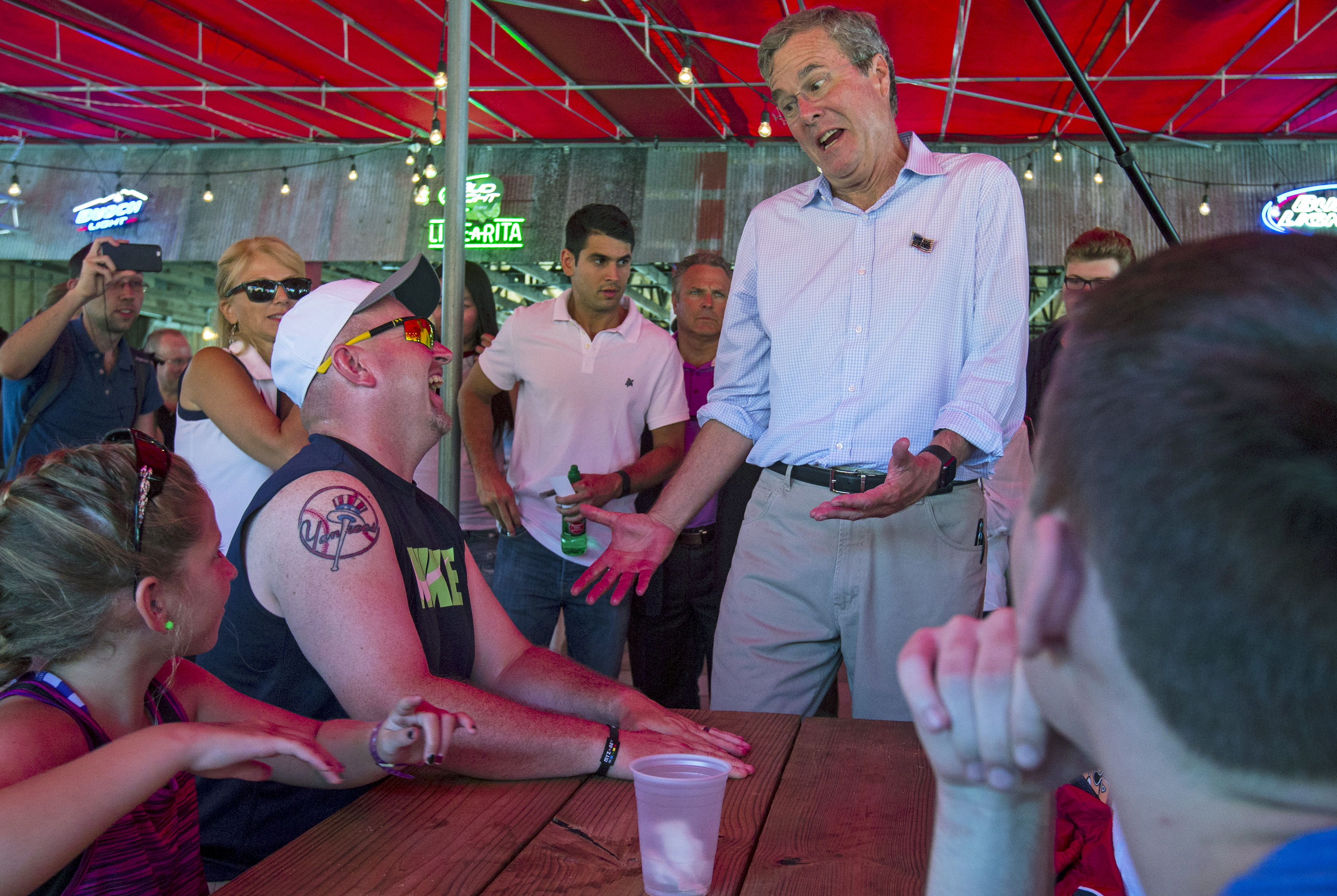 U.S. Republican presidential candidate Jeb Bush (2nd R) shares a laugh with attendees at the Iowa State Fair in Des Moines, Iowa, United States, August 14, 2015. REUTERS/Jim Young  TPX IMAGES OF THE DAY      - RTX1OBBS
