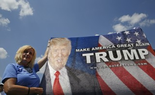 A supporter of U.S. Republican presidential candidate Donald Trump holds up a banner for his arrival near the Iowa State Fair in Des Moines, Iowa, United States, August 15, 2015.  REUTERS/Jim Young   - RTX1ODWB