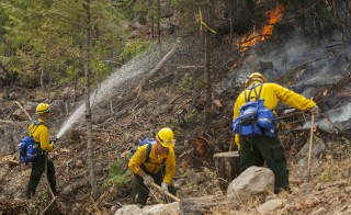 Firefighters from the Washington National Guard battle the First Creek Fire in Chelan, Washington August 18, 2015. Dozens of wildfires burning across the drought-parched U.S. Northwest on Tuesday have destroyed scores of structures, sparked evacuation orders for thousands of people, and killed at least 27 wild horses.  REUTERS/David Ryder - RTX1OQFV