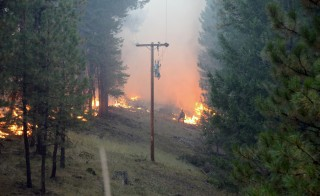 A fire fighter watches flames from a back fire at the Canyon Creek Complex Fire as a power line stands in the foreground in this handout photo taken August 17, 2015 and released to Reuters August 19, 2015. About a dozen large fires are burning across the state, threatening hundreds of structures, authorities said.  REUTERS/Gert Zoutendijk/Oregon State Fire Marshal/Handout ATTENTION EDITORS - THIS PICTURE WAS PROVIDED BY A THIRD PARTY. REUTERS IS UNABLE TO INDEPENDENTLY VERIFY THE AUTHENTICITY, CONTENT, LOCATION OR DATE OF THIS IMAGE. FOR EDITORIAL USE ONLY. NOT FOR SALE FOR MARKETING OR ADVERTISING CAMPAIGNS. THIS PICTURE IS DISTRIBUTED EXACTLY AS RECEIVED BY REUTERS, AS A SERVICE TO CLIENTS. - RTX1OU5H