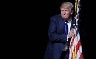 U.S. Republican presidential candidate Donald Trump hugs a U.S. flag as he takes the stage for a campaign town hall meeting in Derry, New Hampshire, August 19, 2015.  Republican candidates are finding their own messages knocked off-kilter on the campaign trail as they're forced to respond to Trump's controversial ideas. Photo by Brian Snyder