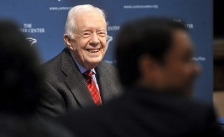 Former U.S. President Jimmy Carter  (C) takes questions from the media during a news conference about his recent cancer diagnosis and treatment plans, as his grandson Jason Carter (R) listens on, at the Carter Center in Atlanta, Georgia August 20, 2015. Carter said on Thursday he will start radiation treatment for cancer on his brain later in the day. Carter, 90, said he will cut back dramatically on his schedule to receive treatment every three weeks after doctors detected four spots of melanoma on his brain following recent liver cancer surgery. REUTERS/John Amis - RTX1OYC8