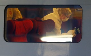 French investigating police in protective clothing films inside the Thalys high-speed train where shots were fired in Arras, France, August 21, 2015. Three people were wounded in a shooting incident on high-speed train between Amsterdam and Paris on Friday, the French Interior Ministry said. A man was arrested when the train stopped at Arras station in northern France but his motives were not yet known, a ministry spokesman said.  REUTERS/Pascal Rossignol - RTX1P4TU