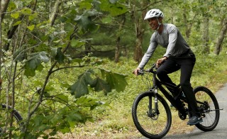 U.S. President Barack Obama takes a bike ride with his family on Martha's Vineyard in Massachusetts August 22, 2015. Obama is on a two-week vacation on the Vineyard.    REUTERS/Kevin Lamarque  - RTX1P7UQ