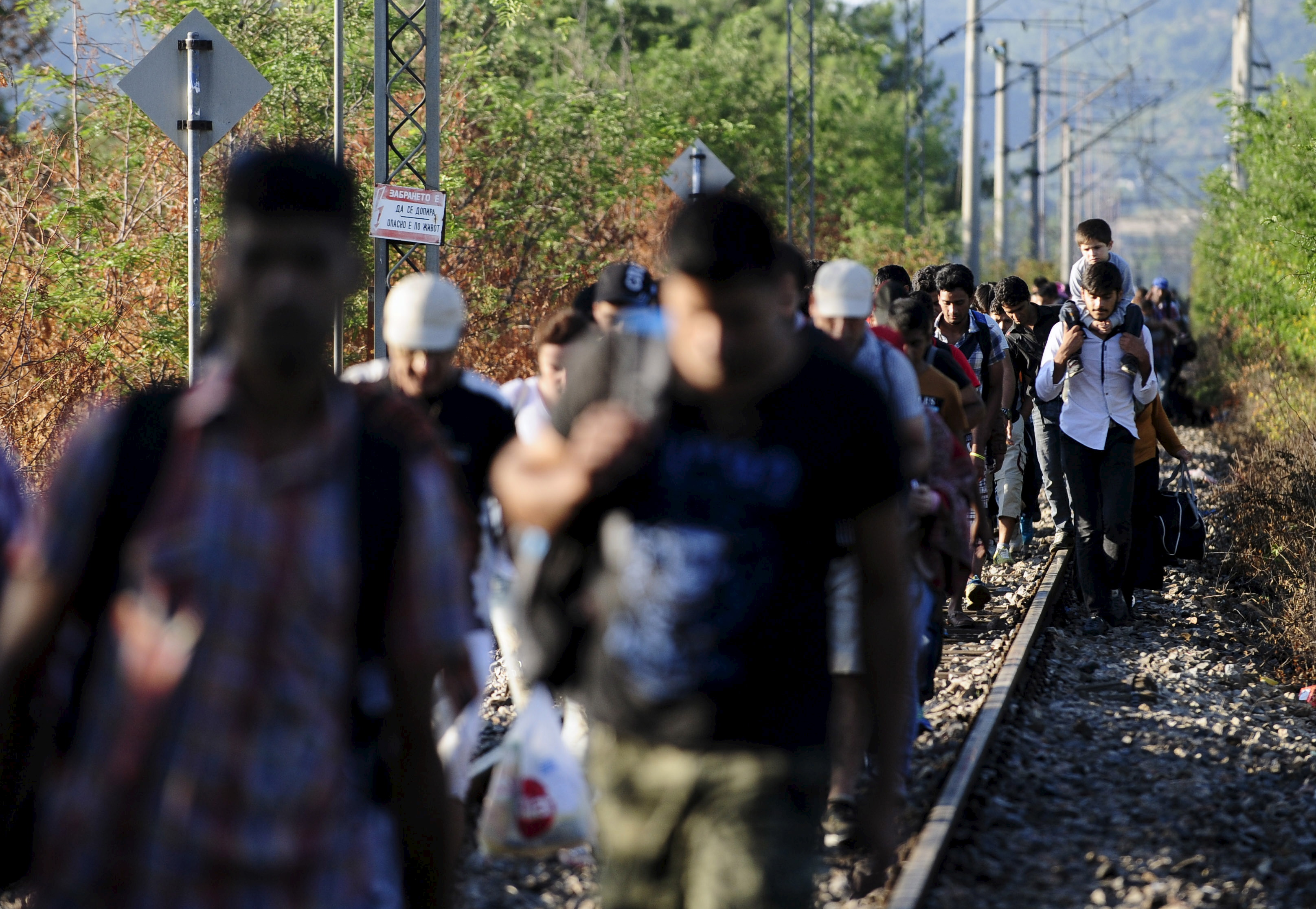 Migrants cross into Macedonia near Gevgelijia, from Greece's border with Macedonia, August 23, 2015. Photo by Ognen Teofilovski/Reuters.