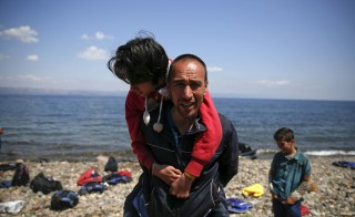 An Afghan migrant carries his daughter, moments after arriving on a dinghy on the island of Lesbos, Greece August 23, 2015. Photo by Alkis Konstantinidis/Reuters.