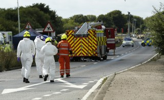Emergency services and crash investigation officers work at the site where a Hawker Hunter fighter jet crashed onto the A27 road at Shoreham near Brighton, Britain August 23, 2015. Photo by Luke MacGregor/Reuters.