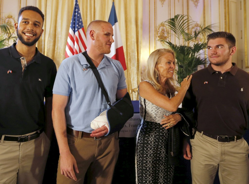 U.S. ambassador to France Jane Hartley (C) presents student Anthony Sadler, U.S Airman First Class Spencer Stone and National Guardsman Alek Skarlatos (L to R) as they attend a ceremony at the U.S. Embassy in Paris, France, August 23, 2015. The three men helped overpower a Kalashnikov-toting attacker on a high speed train heading for Paris from Amsterdam on Friday.   REUTERS/Regis Duvignau - RTX1PBY3