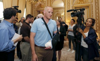 U.S Airman First Class Spencer Stone arrives surrounded by journalists to attend a ceremony at the U.S. Embassy as U.S. ambassador to France Jane Hartley presents him, student Anthony Sadler and National Guardsman Alek Skarlatos in Paris, France, August 23, 2015.  The three men helped overpower a Kalashnikov-toting attacker on a high speed train heading for Paris from Amsterdam on Friday.   Regis Duvignau/Reuters