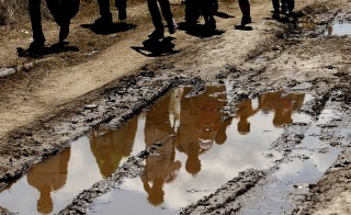 The reflection of migrants is seen in a puddle of muddy water on a road after they crossed the Greek-Macedonian border into Macedonia, near Gevgelija August 24, 2015. State authorities and aid agencies threw up tents and scrambled to supply food and water to thousands surging through the western Balkans, their numbers swelling since Greece began ferrying migrants from its overwhelmed islands to the mainland. The United Nations refugee agency, UNHCR, said more than 7,000 had reached Serbia from Macedonia between Saturday and Sunday, many of them having spent three desperate days on Greece's northern border after Macedonia halted their passage saying it could take no more.   REUTERS/Ognen Teofilovski - RTX1PFGQ