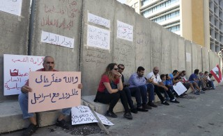 "People sit along a concrete barrier erected by security forces on Aug. 24 to protect government buildings after protests over corruption turned violent. One banner reads, ""I swear to God, I thought I was at the borders with Israel."" Photo by Mohamed Azakir/Reuters"