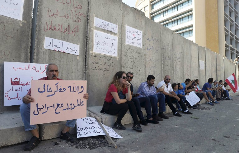 """People sit along a concrete barrier erected by security forces on Aug. 24 to protect government buildings after protests over corruption turned violent. One banner reads, """"I swear to God, I thought I was at the borders with Israel."""" Photo by Mohamed Azakir/Reuters"""