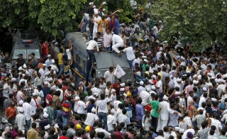 Members of the Patel community climb a police vehicle as they attend a protest rally in Ahmedabad, India, August 25, 2015. Thousands of the community members on Tuesday held the huge protest rally to demand reservation for their community, local media reported. REUTERS/Amit Dave - RTX1PL0V