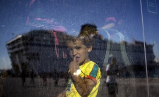 A migrant child is seen through a bus window as the Eleftherios Venizelos passenger ship is reflected on it following its arrival at port of Piraeus near Athens, Greece, August 25, 2015. Greece said on Monday its infrastructure was insufficient to cope with the waves of refugees flowing into the country in one of the worst humanitarian crises Europe has faced since the World War Two.  REUTERS/Stoyan Nenov       TPX IMAGES OF THE DAY      - RTX1PLP9