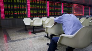 An investor takes a nap in front of an electronic board showing stock information at a brokerage house in Beijing, August 26, 2015. Asian shares struggled on Wednesday as investors feared fresh rate cuts in China would not be enough to stabilise its slowing economy or halt a stock collapse that is wreaking havoc in global markets. REUTERS/Jason Lee  - RTX1PNY1